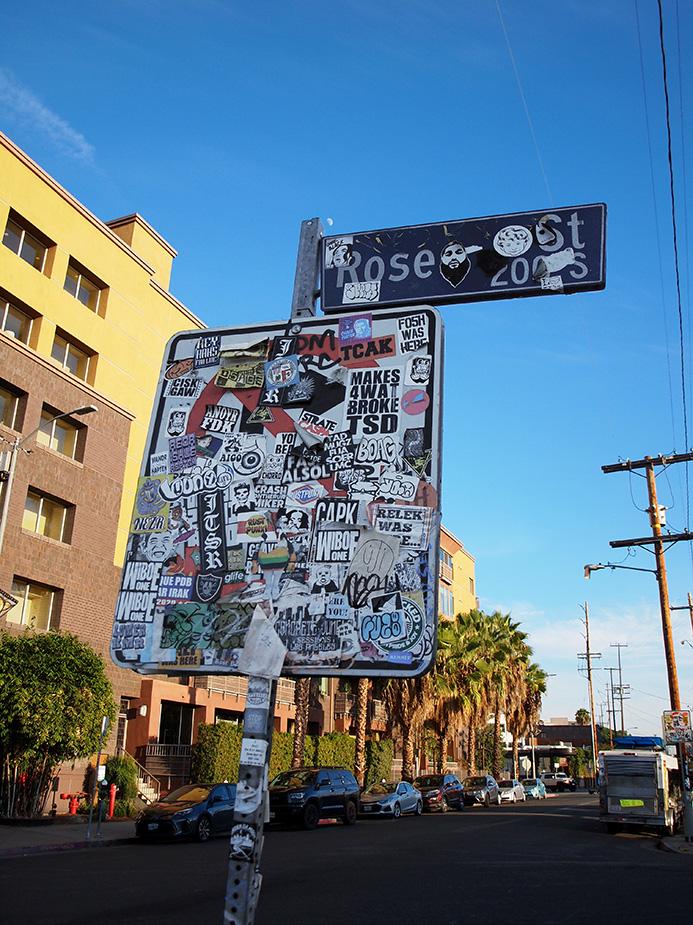 Panneau de signalisation recouvert d'autocollants à Art District L.A.